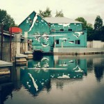 Intentionally upside-down street art that people appreciate it in reflection on the surface