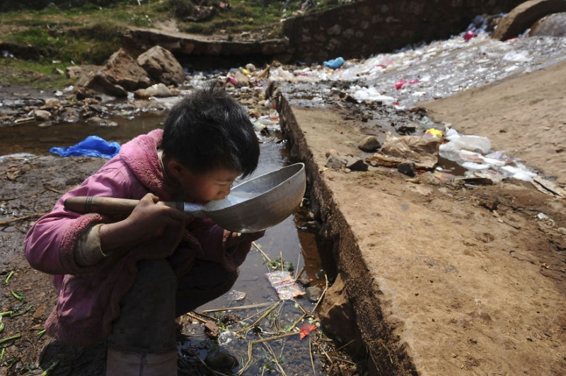 A child drinks water near a stream in Fuyuan county, Yunnan province March 20, 2009. World Water Day will be observed on March 22. Picture taken March 20, 2009. (Photo by Reuters/Stringer)