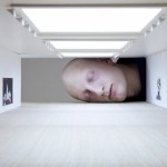 Surreal photography of giant heads inside famous art exhibition spaces