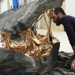 Unique sculptures of still molten bronze bonding with stone