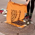 Pirate printers create inspirational T-Shirt and bag designs with manhole covers on the stree