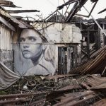 Street artist paints intimate portraits on wall of abandoned buildings that look like they're telling stories hidden inside the houses