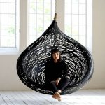 Dramatic hanging chair made from black volcanic basalt fibre